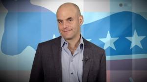 Peter Sagal smirking with Democratic Donkey background